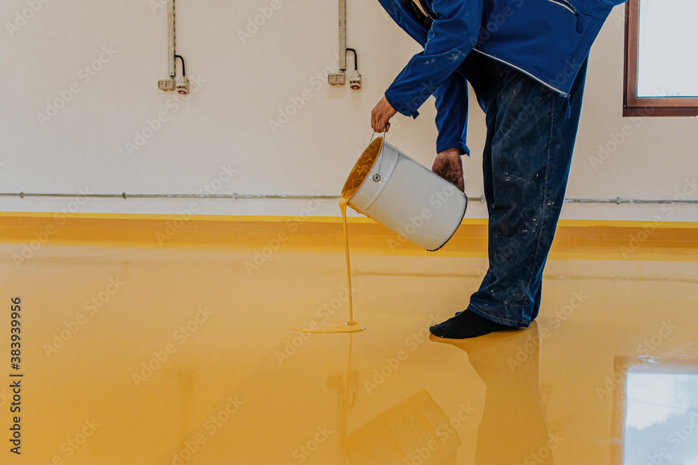 Fototapeta Worker, coating floor with self-leveling epoxy resin in industrial workshop.