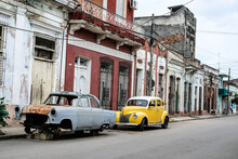 Small Yellow Car And Broken Blue Car Parked On The Street In Cuba