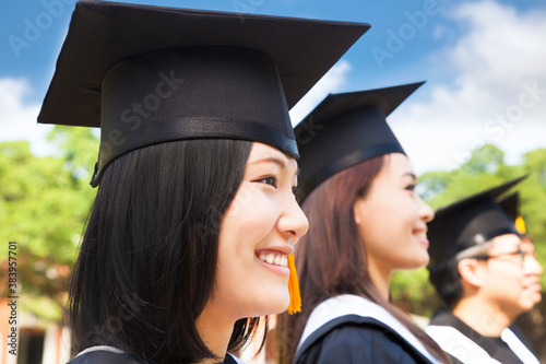 smiling female college graduate standing with classmate