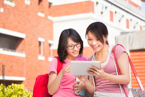 two students using a tablet to discuss homework