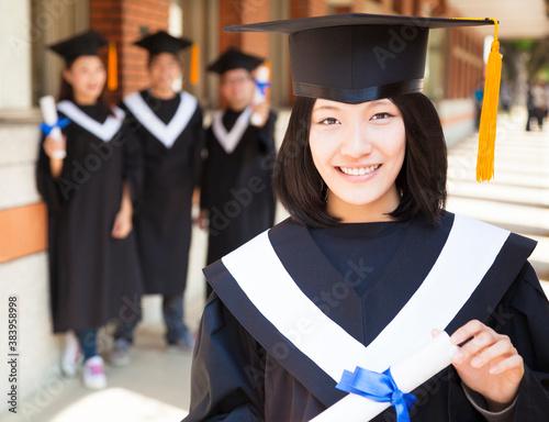 pretty female college graduate holding diploma with classmates