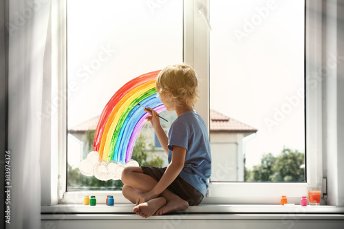 Fototapeta Little boy drawing rainbow on window indoors. Stay at home concept obraz