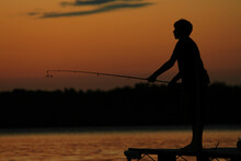 Silhouette Of Boy Fishing Off Pier At Sunset