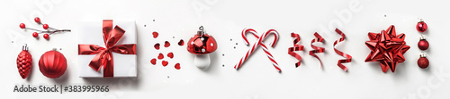 Fototapeta Christmas decoration, gift boxes with red ribbon, sparkles, confetti, christmas candy and balls on white background. Xmas and Happy New Year holiday. Flat lay, top view, wide composition obraz