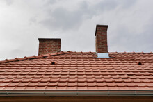 Home Roof With Red Tiles And Dramatic Rains Clouds In The Background. Weather Disasters Concept
