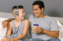 Son Listening To Music And Sitting With Father On Couch