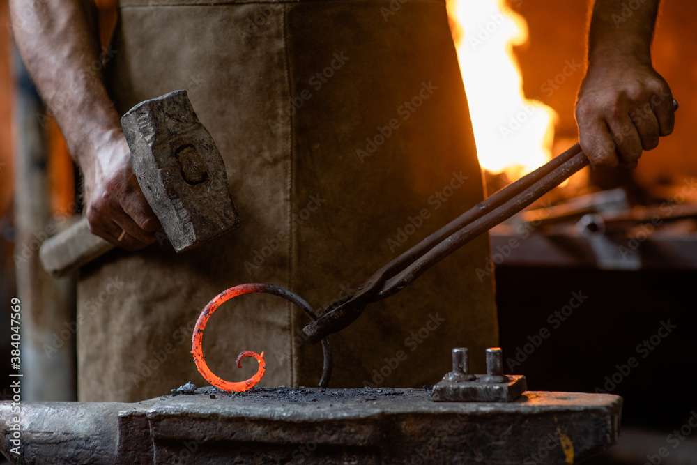 Fototapeta Old blacksmith is processing a hot metal object of a spiral shape on the anvil in the forge