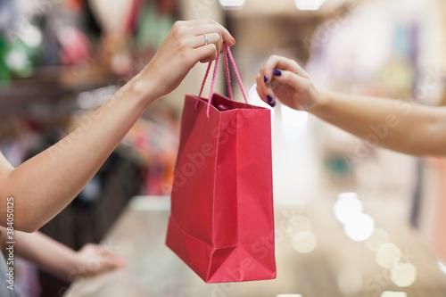Woman handing over shopping bag Canvas