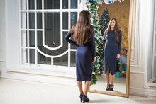 Brown-haired Wearing Blue Dress And Blue Shoes Girl Stands Before Xmas Decorated Mirror At Drawing-room