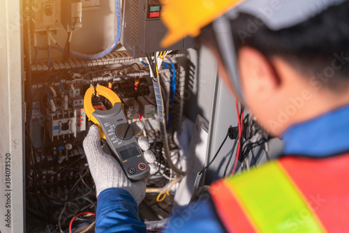 Digital clamp meter in hands of electrician close-up against background of electrical wires and relays Wallpaper Mural