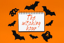 Happy Halloween Holiday Concept. Notepad With Text The Witching Hour On White And Orange Background With Bats, Pumpkins And Ghosts