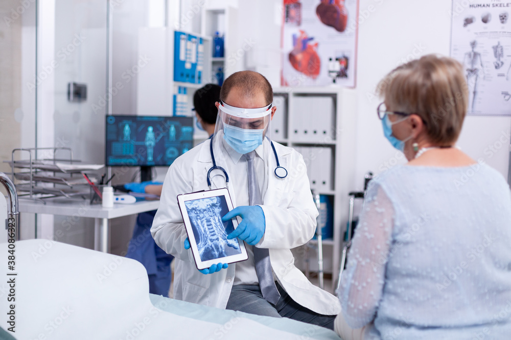Fototapeta Doctor in hospital room explaining x-ray on tablet for senior woman during consultation in clinic room. Medical examination for infections, disease and diagnosis.
