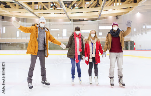 people, friendship, gesture, sport and leisure concept - friends wearing face protective medical masks for protection from virus disease waving hands on skating rink