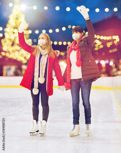christmas, winter and leisure concept - two women or friends wearing face protective medical masks for protection from virus disease waving hands at outdoor skating rink over holiday lights background