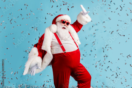 Obraz Photo of pensioner old man grey beard careless north pole closed party dance having fun colorful confetti wear santa x-mas costume suspender sunglass cap isolated blue color background - fototapety do salonu