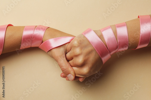 Women shaking hands with pink ribbons on beige background