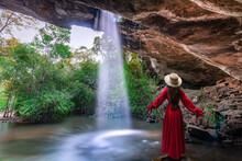 Asian Woman Standing On The Rock At Saeng Chan Waterfall (Long Ru Waterfall), Thailand.