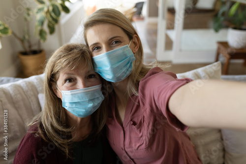 Senior woman and her daughter wearing face mask taking selfie at home