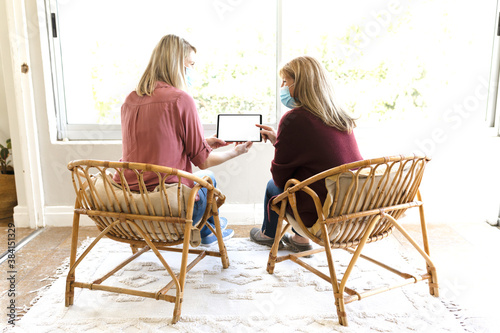 Senior woman and her daughter wearing face mask using digital tablet at home