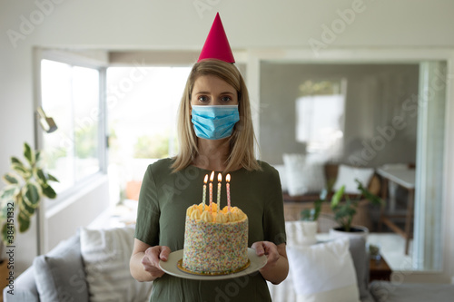 Portrait of woman wearing face mask holding a cake at home