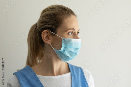 Female health worker wearing face mask against white background