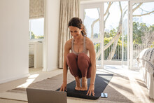 Woman Watching Online Exercise Class And Working Out At Home