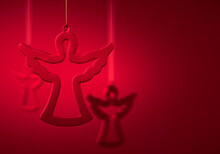 Three Hanging Glass Silhouettes Of Angel Against Burgundy Red Background.