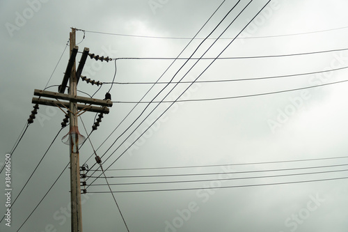Papel de parede Electric pole with many cable under dark clouds before rainy.