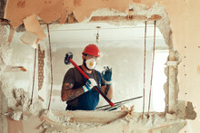 Builder With A Hammer In His Hands Breaks The Cement Wall The Builder Is Dressed In A Protective Suit And Helmet