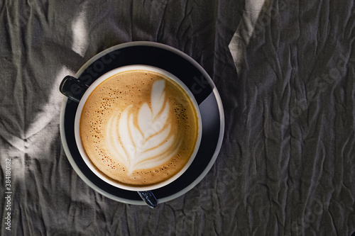 Coffee with latte art on grey tablecloth, top view Billede på lærred