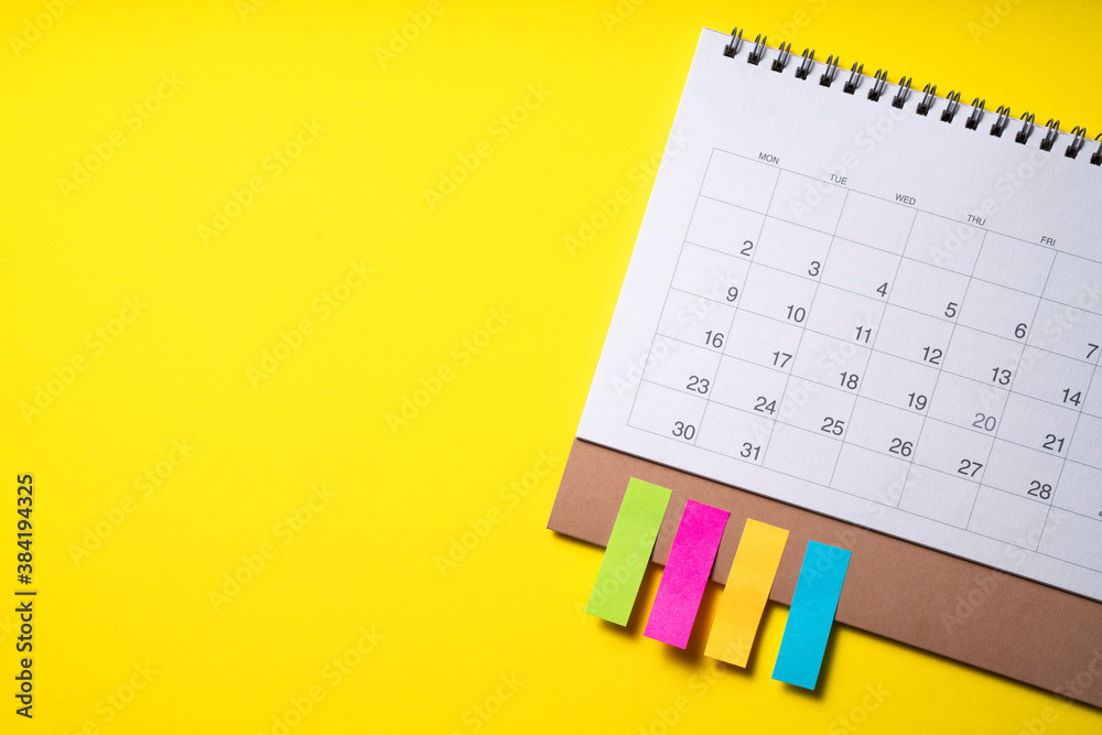 Fototapeta close up of calendar on the yellow table background, planning for business meeting or travel planning concept