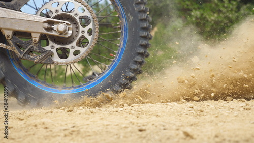 Close up wheel of powerful off-road motorcycle spinning and kicking up dry ground Fototapet