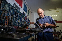 Old Mechanic Working In His Wo...