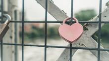 A Heart Shaped Lock On A Metal Grid Of A Bridge