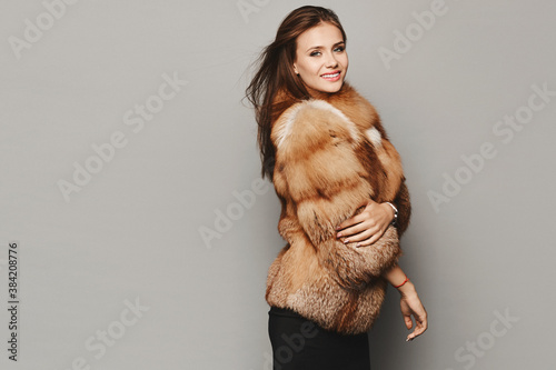 Fotografie, Obraz Side view of a model girl in an expensive luxurious fur coat isolated at the grey background
