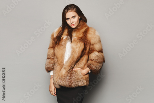 Obraz na plátně Model girl in a luxurious winter fur coat on the grey background, isolated