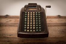 Vintage Adding Machine Sitting On Old Wooden Trunk
