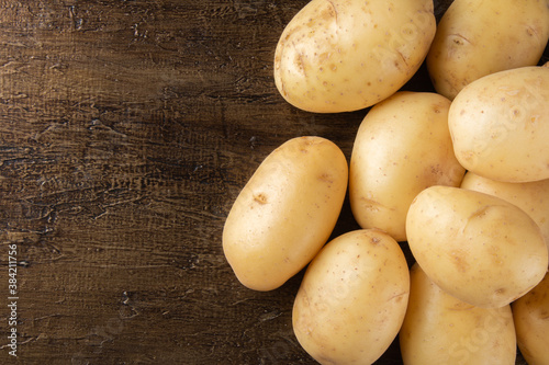 Photo Pile of potatoes lying on rustic background. Top view.