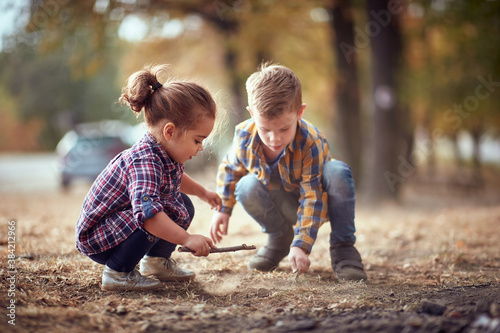 Fototapeta Little brother and sister playing in the dirt in the forest