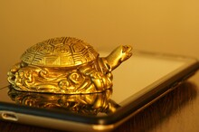 Metal Turtle On A Mobile Phone.
