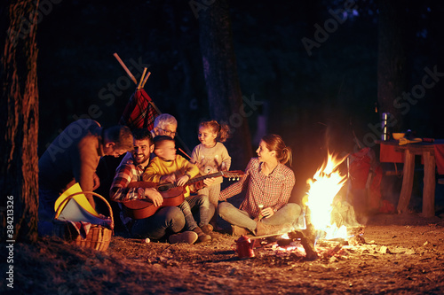Obraz A happy family having a good time around a campfire in the forest - fototapety do salonu
