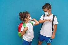Children Wearing Face Protective Mask Going Back To School During Corona Virus Pandemic - Little Kids Doing New Social Distance Greeting Bumping Elbows - Healthcare And Education Concept