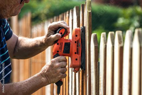 Fotomural Sanding wood fence by sander