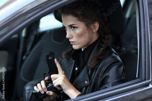 Fotografia Girl driving a car with a gun in her hands