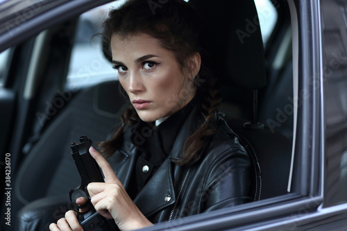 Tablou Canvas Girl driving a car with a gun in her hands
