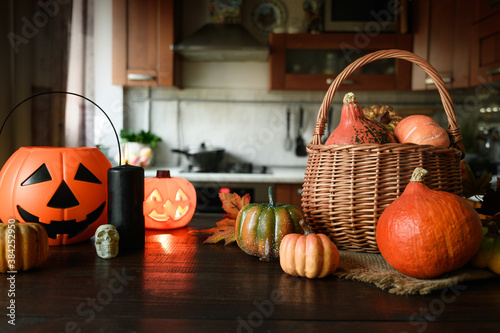 Domestic Halloween party with pumpkins on tabletop and blurred kitchen as backdrop.