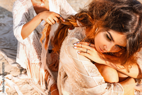 Fotografía two beautiful young woman in elegant boho dresses oudoors at sunset