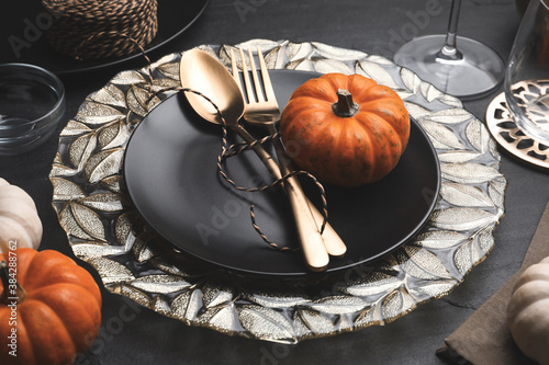 Autumn table setting with golden cutlery and pumpkin on black background