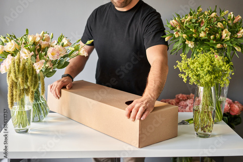 Valokuva Step by step a male florist puts a set of flowers in a carton box