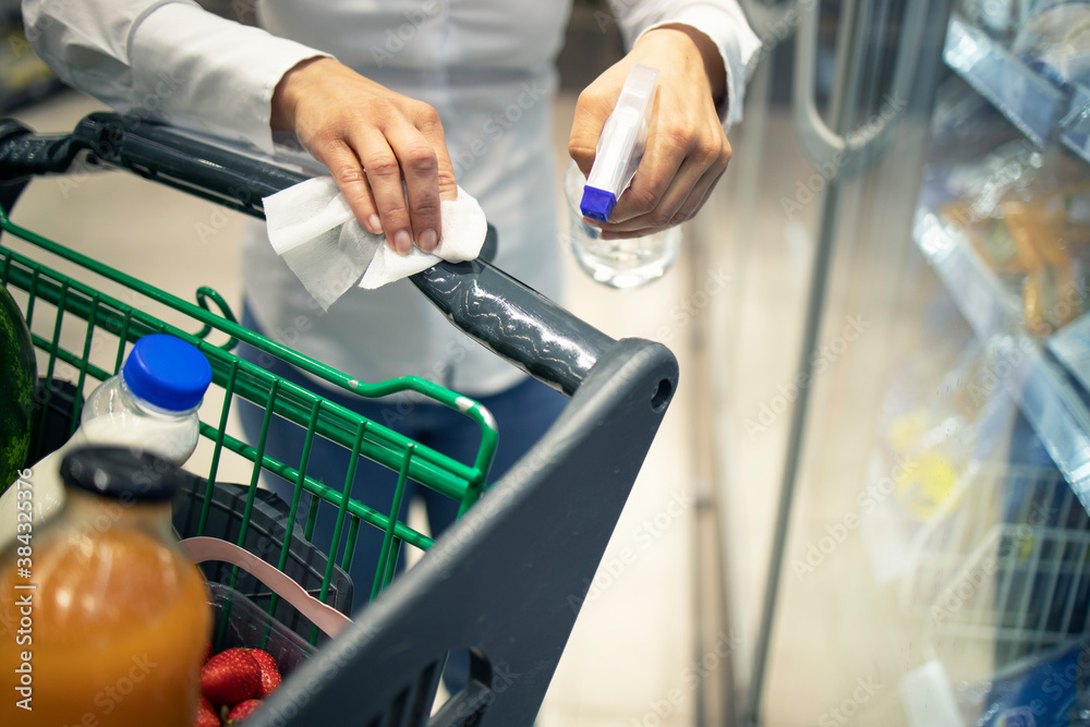 Fototapeta Wiping handlebars of the shopping cart. Woman disinfecting shopping cart with sanitizer before use against corona virus or covid-19. Protective measures to stay healty durin coronavirus pandemic.